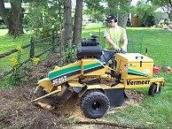 James operating a stump grinder.